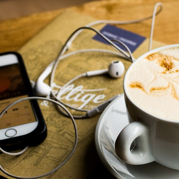 iPhone, headphones and a cup of coffee